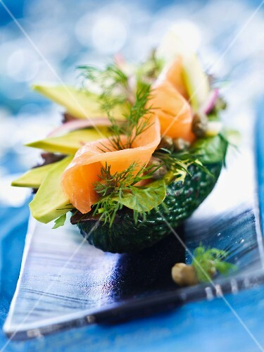 An avocado shell filled with avocado, smoked salmon, capers, salad leaves and dill