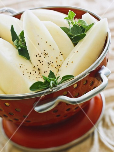 Raw potato wedges with sage leaves before cooking