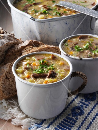 Two mugs of Polish mushroom soup with a saucepan and rye bread
