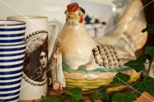 Mugs and a Chicken shaped egg dish, sitting on the shelf