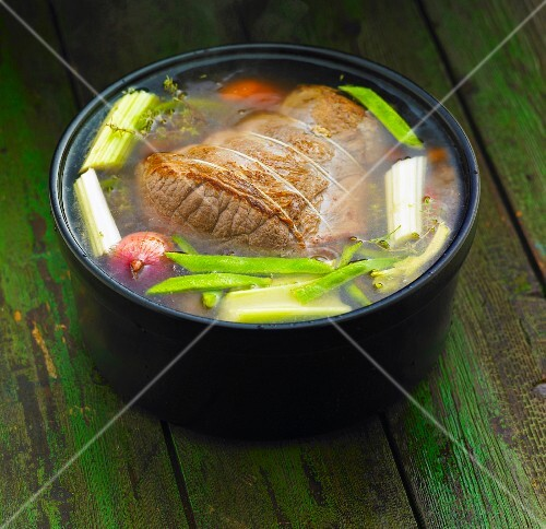 Beef joint with vegetables cooking in pot
