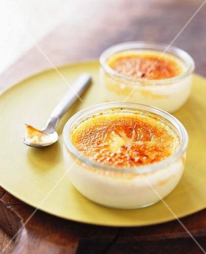 Two glass ramekins of crème brûlée