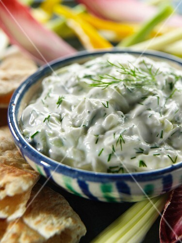 A bowl of greek tsatziki with pitta bread and crudites editorial food