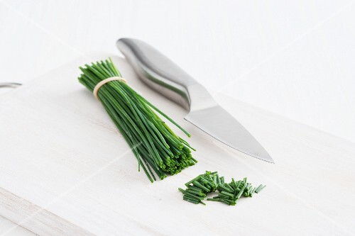 A bunch of chives and a knife on a chopping board