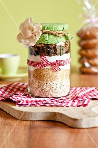 A jar containing dry ingredients for making walnut and oat biscuits with chocolate chips