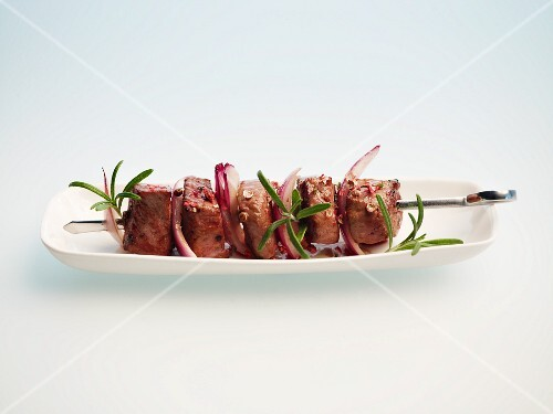 A lamb kebab on a plate against a white background