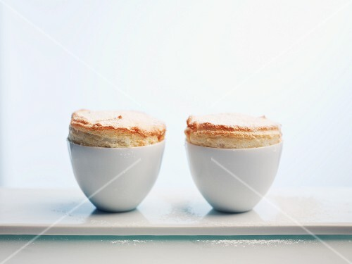 Two passion fruit soufflés against a white background