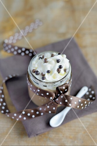 Mousse au chocolat topped with whipped cream in a screw-top jar
