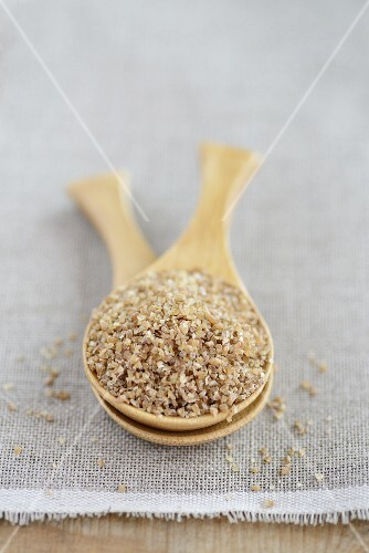 Bulgur (coarse-ground wheat) in a wooden spoon