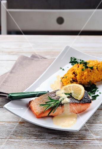 Grilled salmon with rosemary and lemon sauce served with yellow risotto