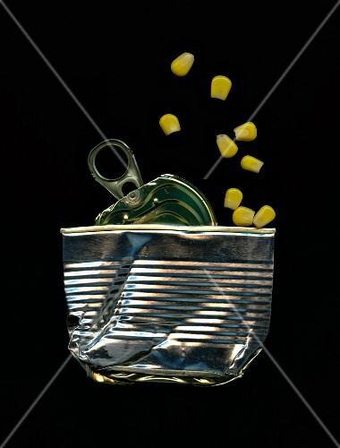 A flattened tin with pieces of sweetcorn
