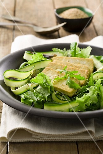 Fried tofu on a bed of salad with courgette strips