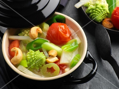 Delicate vegetable ragout in a black mini casserole pot
