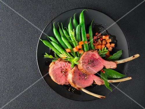 Lamb chops with beans and diced tomato on a black plate