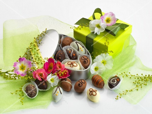 Easter chocolates in a tin with green tulle, primroses and a gift box