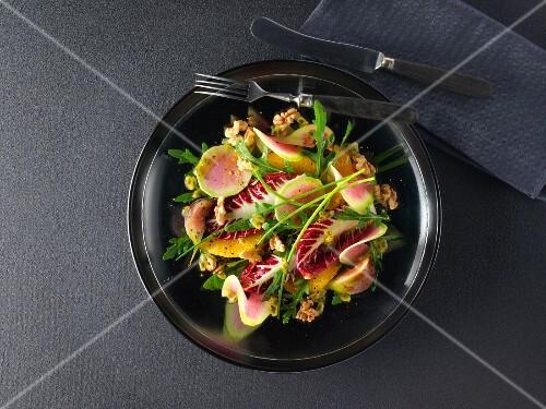 Gemischter Salat mit bunten Radieschen, Orangen, Feigen, Walnüssen und Maracuja