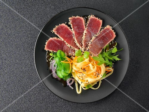 Tuna sashimi with sesame seeds, carrot strips and wide noodles