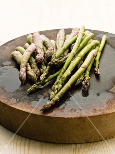 Fresh green asparagus on a round wooden board