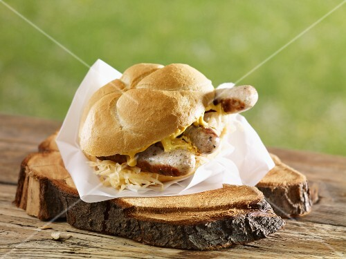 Bread roll filled with sauerkraut, grilled bratwurst and sausages