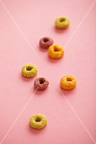 Pieces of breakfast cereal on a pink surface