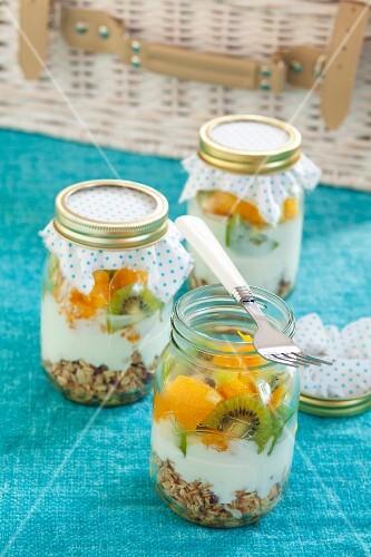 Three jars containing ingredients for muesli: rolled oats, yoghurt, kiwi and orange