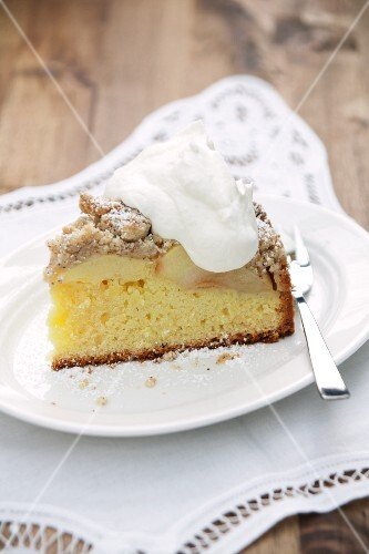 A slice of apple cake with crumble topping and cream