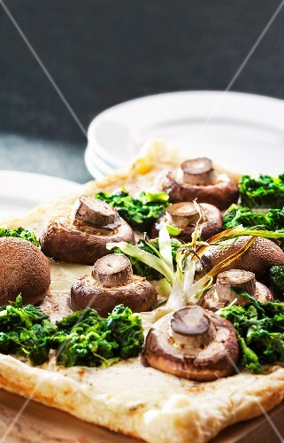 Puff pastry tart topped with fresh mushrooms and spinach