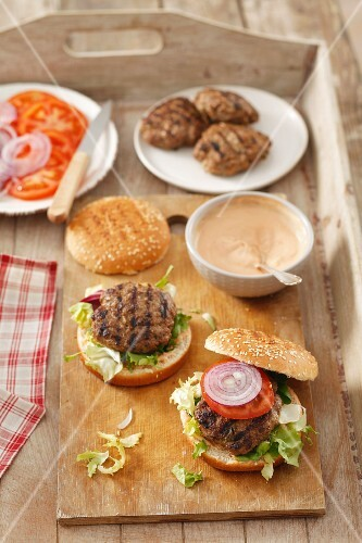 Home-made burgers with burger constituents on a wooden tray