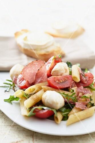 Pasta salad with tomatoes, salami, mozzarella and rocket