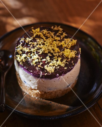 A small cheesecake with blueberries and lemon zest