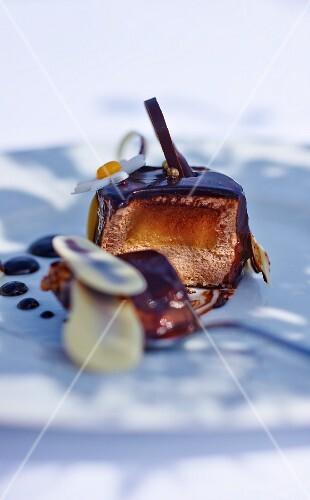 An individual chocolate and caramel cake with bananas, sliced into