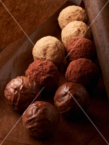 Assorted chocolate truffles on grease-proof paper