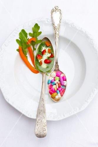 A spoonful of herb sauce with peppers and a spoonful of vitamin pills