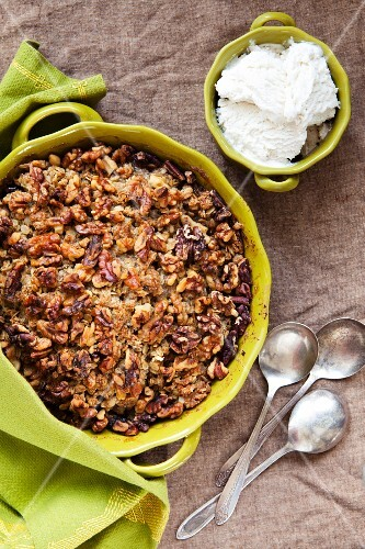 Gluten Free Apple Crisp in a Green Baking Dish with a Bowl of Vanilla Bean Ice Cream