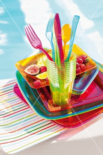 Plastic tableware and fruit by the swimming pool