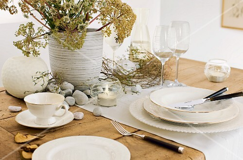 Table set with crockery, glasses and objects from nature