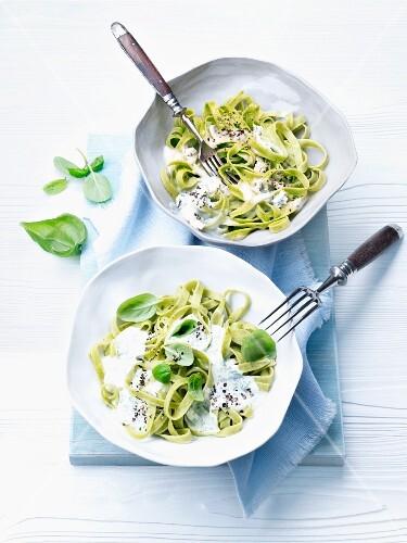 Green ribbon pasta with cream sauce and basil