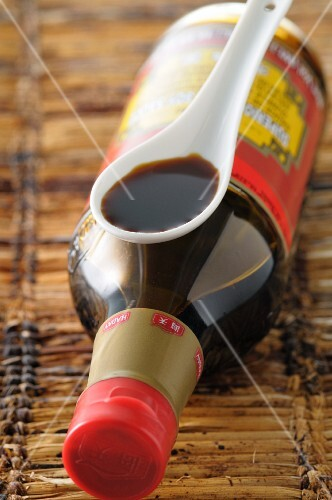 Soy sauce in a bottle and on a spoon