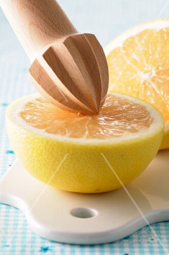 A halved grapefruit with a wooden lemon squeezer