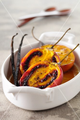 Baked tamarillos with vanilla pods in a casserole dish