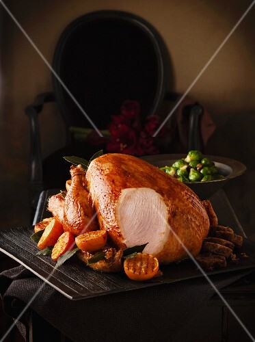 Roast turkey with clementines and Brussels sprouts, partly sliced