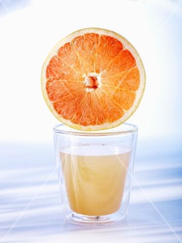 Half a grapefruit on top of a glass of grapefruit juice