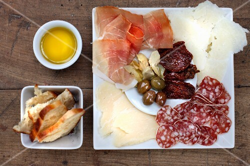 Antipasti: sundried tomatoes, olives, parmesan, Parma ham, olive oil, bread, salami, pickled artichokes