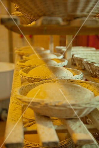 Baking baskets filled with bread dough on a set of shelves