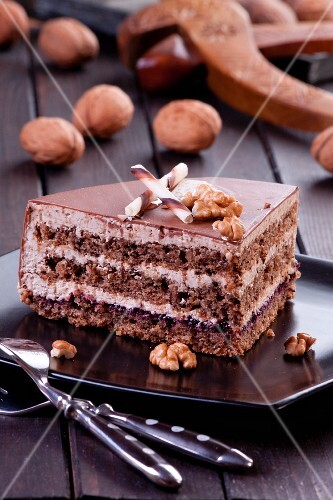 A slice of walnut layer cake with chocolate curl