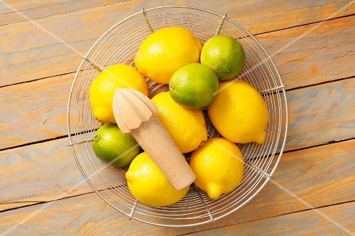 Lemons and limes in a wire basket with a lemon squeezer
