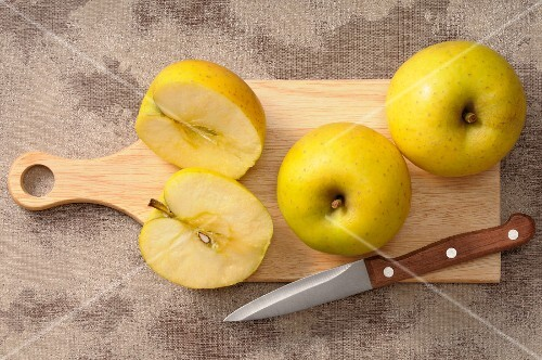 Golden Delicious apples, whole and halved, on a chopping board