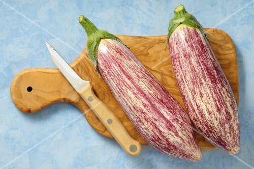 Two aubergines on a chopping board with a knife