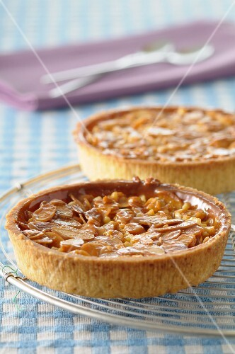 Two almond tarts on a cooling rack
