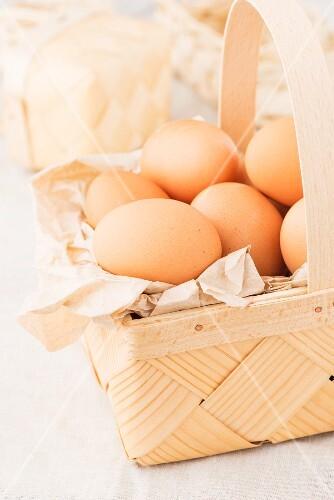 Fresh brown eggs in a woodchip basket